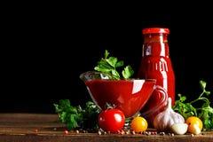 Todavía vida de tomates y de la salsa de tomate frescos en los tableros de madera En un fondo negro Imágenes de archivo libres de regalías