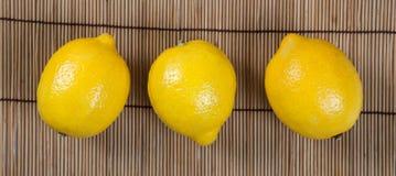 Todavía vida de tres limones frescos en una servilleta de bambú Imagen de archivo
