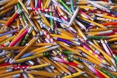 Todavía vida de un arsenal al azar de Bien-utilizado coloreado brillantemente escritura de los lápices Imagen de archivo libre de regalías