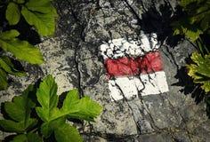 Todavía vida de una marca turística roja en piedra Fotos de archivo