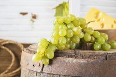 Todavía vida de uvas rojas en un barril de madera Foto de archivo