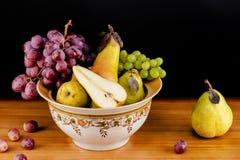 Todavía vida de uvas y de peras maduras Imagenes de archivo
