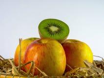 Todavía vida del kiwi y de la manzana en cesta en el fondo blanco Fotos de archivo