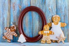 Todavía vida del pan de jengibre, hombres de pan de jengibre, marco marrón en el fondo de madera azul, tarjeta de felicitación de Imagen de archivo libre de regalías