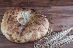 Todavía vida del pan Pita cocido, de los oídos del trigo y de los granos dispersados Imagen de archivo