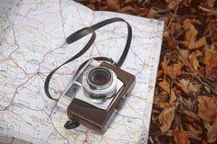 Todavía vida en el bosque del otoño con la cámara y el mapa Foto de archivo