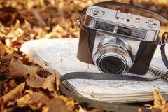 Todavía vida en el bosque del otoño con la cámara y el mapa Imagen de archivo libre de regalías