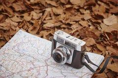 Todavía vida en el bosque del otoño con la cámara y el mapa Fotos de archivo libres de regalías
