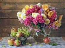 Todavía vida en estilo rústico con los crisantemos, las uvas y la manzana Imagen de archivo
