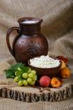 Todavía vida en un estilo rústico: requesón en un plato, una leche y frutas de la arcilla en fondo de madera Imagen de archivo libre de regalías