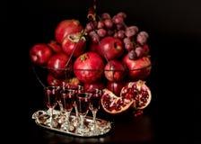 Todavía vida en un fondo oscuro Vidrios del vino (licor), frutas a Fotos de archivo