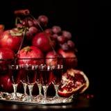 Todavía vida en un fondo oscuro Vidrios del vino (licor), frutas a Imagenes de archivo