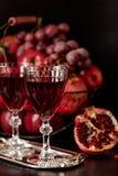Todavía vida en un fondo oscuro Vidrios del vino (licor), frutas a Fotografía de archivo