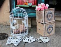 Todavía vida - jaula de pájaros decorativa del vintage con la estatua de un gato y de cajas hechas a mano de madera con las rosas Imágenes de archivo libres de regalías