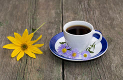 Todavía vida a la taza de café y de una flor amarilla en una tabla Fotografía de archivo libre de regalías