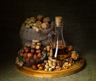 Todavía vida; nueces, cacahuetes, avellanas, aceite de nuez, en el tablero imagen de archivo libre de regalías