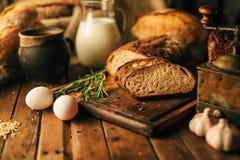 Todavía vida 1 Productos agrícolas: huevos, leche, pan fresco en una tabla de madera Truco del primer uno fotografía de archivo