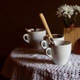 Todavía vida 1 Tazas blancas de la porcelana y un florero del soporte de flores en una tabla con un mantel blanco en un pasillo m Foto de archivo