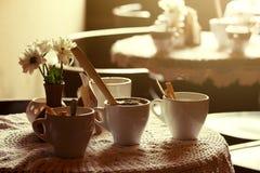 Todavía vida 1 Tazas blancas de la porcelana y un florero del soporte de flores en una tabla con un mantel blanco en un pasillo m Imagenes de archivo