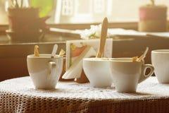 Todavía vida 1 Tazas blancas de la porcelana y un florero del soporte de flores en una tabla con un mantel blanco en un pasillo m Fotos de archivo libres de regalías