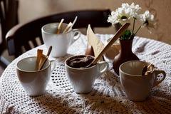 Todavía vida 1 Tazas blancas de la porcelana y un florero del soporte de flores en una tabla con un mantel blanco en un pasillo m Fotografía de archivo
