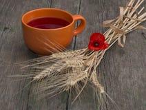 Todavía vida una taza de la arcilla con el jugo, el trigo y una flor de la amapola Fotos de archivo libres de regalías