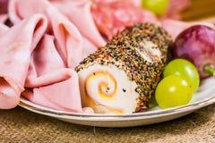 Todavía vida - vista ascendente cercana de la uva de moscatel amarilla y roja, del queso adornado y del salami en una placa blanc Imagen de archivo libre de regalías