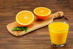 Todavía vidrio de la vida de zumo de naranja fresco en la tabla de madera del vintage con el espacio de la copia Foto de archivo