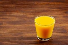 Todavía vidrio de la vida de zumo de naranja fresco en la tabla de madera del vintage con el fondo del espacio de la copia Imagenes de archivo