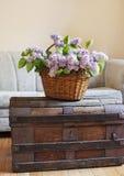 Todavía detalles interiores de la vida, ramo de lila en cesta en tronco Imagen de archivo libre de regalías