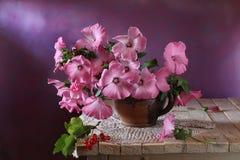 Todavía vida con las flores rosadas en la tabla Fotografía de archivo