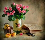 Todavía vida con las rosas, el melocotón y el libro Imagenes de archivo