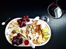 Today is about cheese and wine. Cheese platter with fruits and nuts Stock Photography