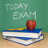 Today exam. Written on a chalkboard. Books, pencils and an apple on foreground royalty free stock photos