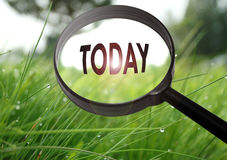 Today. Magnifying glass with the word today on grass background. Selective focus Royalty Free Stock Images