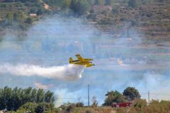 Wildfire Burning Massive Yellow Plane Releases Water stock photos