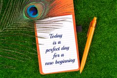 Today is a perfect day for a new beginning. Text in notebook with peacock feather , pen and heart shape on grass Royalty Free Stock Photos