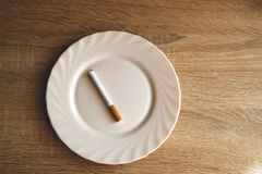 Today`s breakfast in the morning comon. Cigarette on a plate as a synonym for breakfast smoker Royalty Free Stock Images
