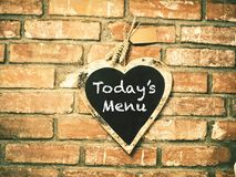 Today`s menu on heart shape chalkboard on concrete wall, restaur. Ant background concept Royalty Free Stock Image