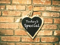 Today`s menu on heart shape chalkboard. On concrete wall, restaurant background concept Stock Image