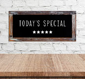 Today's special on vintage chalk board over cement wall and empt. Y wood table background, food and dinks, food display montage Stock Images