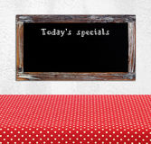 Today's special on vintage chalk board over empty red polka dot Stock Photo
