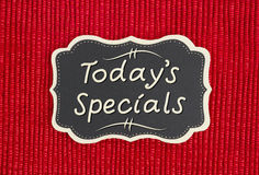 Today`s Specials sign. Today`s Specials hand lettering text on a chalkboard on a shiny red material stock photography