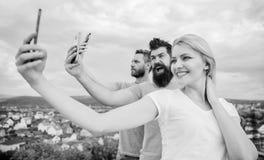 Today selfie ?adna kobieta i m??czy?ni trzyma smartphones w r?kach Ludzie ciesz? si? selfie strzelanin? na naturalnym krajobrazie fotografia stock