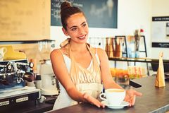Todays good mood is sponsored by coffee. Woman barista in coffee shop. Barista serve cup of hot coffee drink with smile. Pretty woman stand behind cafe counter stock photo