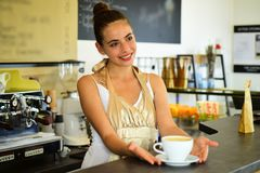 Todays good mood is sponsored by coffee. Woman barista in coffee shop. Barista serve cup of hot coffee drink with smile. Pretty woman stand behind cafe counter stock image