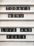 Todays menu is love and peace. Todays menu : love and peace, wood background royalty free stock photo