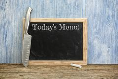 Todays menu written on chalkboard and chefs knife. Today`s menu written on vintage chalkboard and chef`s knife on rustic wooden background royalty free stock photos