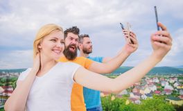 Todays selfie. Pretty woman and men holding smartphones in hands. People enjoy selfie shooting on natural landscape royalty free stock images