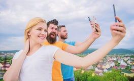 Todays selfie. Pretty woman and men holding smartphones in hands. People enjoy selfie shooting on natural landscape. Todays selfie. Pretty women and men holding royalty free stock images